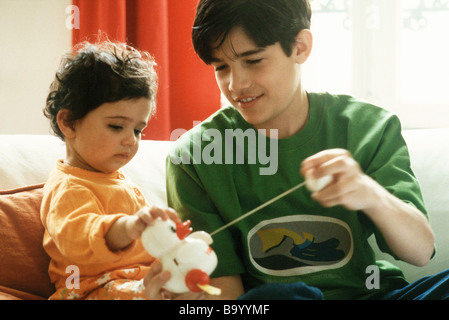 Boy playing with little sister and toy duck - Stock Photo