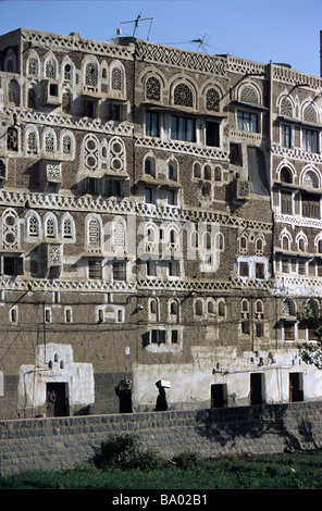 Adobe Mud Brick Tower Houses with Decorated Windows, Sana'a or San'a, Capital of the Republic of Yemen - Stock Photo