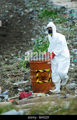 Person in protective suit carrying barrel of hazardous waste - Stock Photo