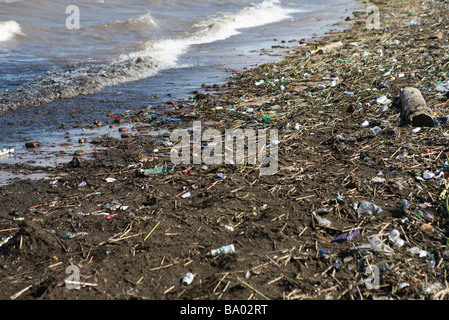 Shore littered with trash and debris - Stock Photo