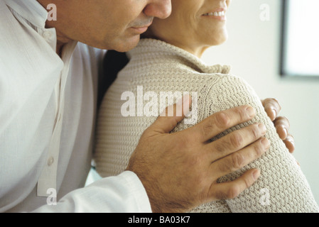 Husband embracing wife from behind, cropped - Stock Photo