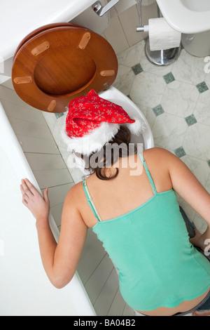 woman vomiting down a toilet - Stock Photo