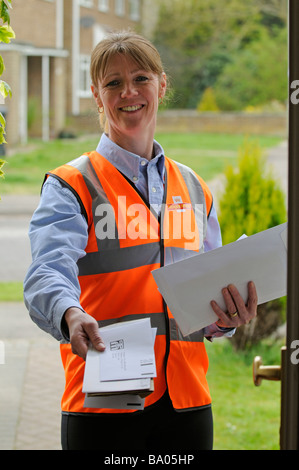 royal mail post woman delivering mail to a customer - Stock Photo