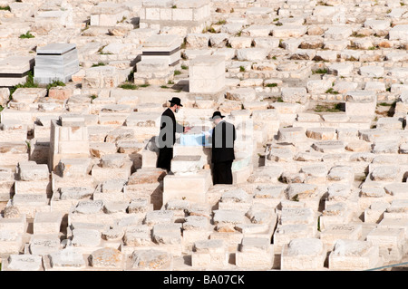 Orthodox Jews prying at one of the tombs in the cemetery on the Mount of Olives Jerusalem, Israel - Stock Photo