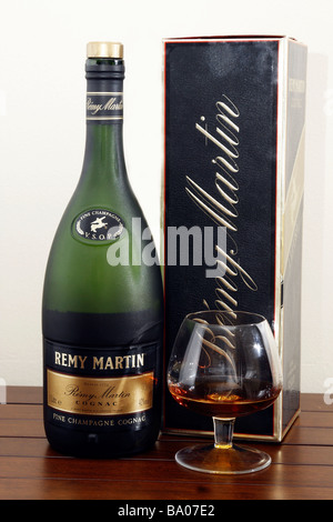 A bottle of Remy Martin VSOP Cognac and a glass of cognac on table. Isolated - cutout - Stock Photo