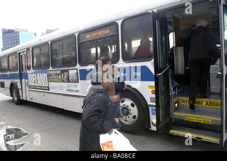 A family boards the B60 bus on Queens Boulevard in the New York borough of Queens - Stock Photo