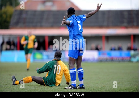 A footballer protests his innocence after another player is left on the ground after a tackle - Stock Photo