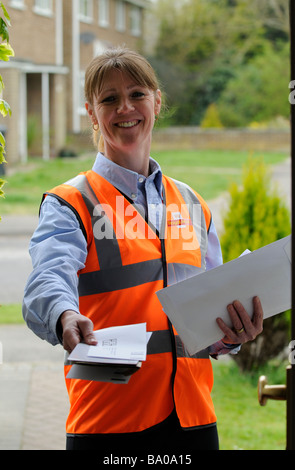 royal mail postwoman delivering mail to a customer - Stock Photo