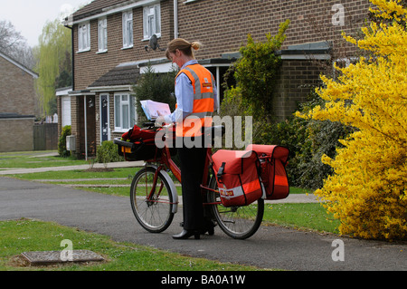 Royal Mail postwoman sorting letters on her round - Stock Photo