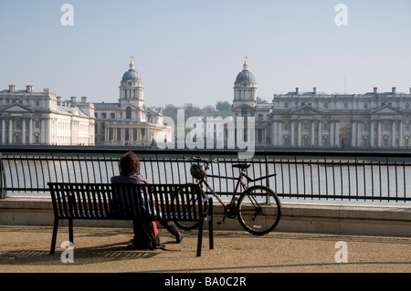 Lady sitting on bench in front of the Old Royal Naval College, in Greenwich, London, England - Stock Photo