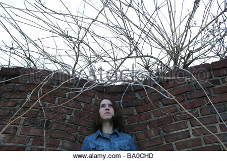 A teenage girl standing next to a brick wall, with tangled branches surrounding her. - Stock Photo