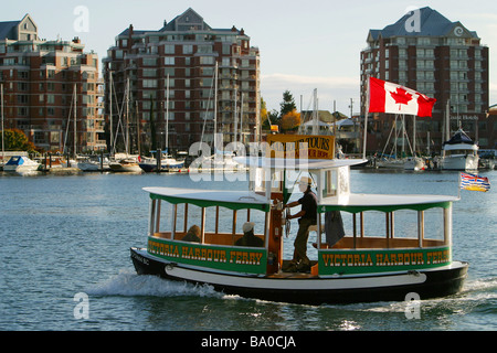 A small passenger ferry, known as a 'Harbour Ferry' takes passengers on a tour around Victoria,BC's, Inner Harbour. - Stock Photo