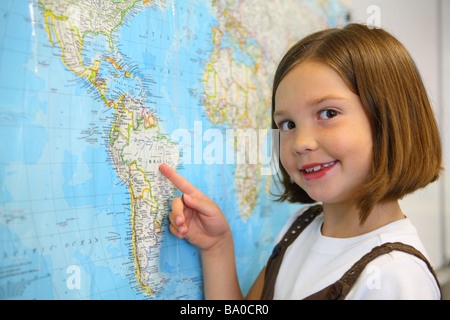 School girl pointing to country on map - Stock Photo