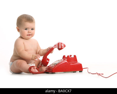 Baby with red telephone on white background - Stock Photo