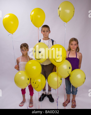 kids and balloons neutral face expression - Stock Photo