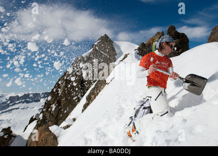 Skier digging snow in the mountains, Chamonix, France - Stock Photo