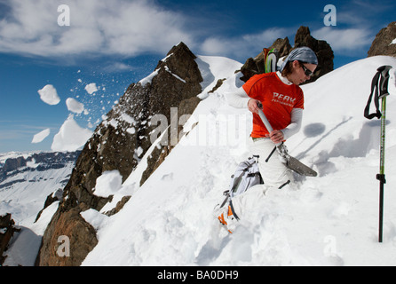 Skier digging a pit in snow in the mountains (snow analysis / avalanche hazard assesment) - Stock Photo
