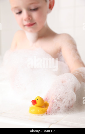 Young boy playing with rubber duckie in bath - Stock Photo