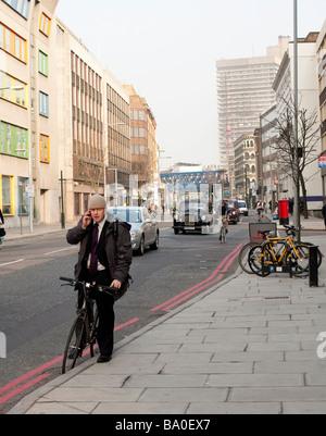 4th April 2009 London mayor Boris Johnson stops to take a phone call on his bicycle on Southwark Street - Stock Photo