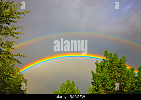 Rainbow forming during a thunder storm in the city of Regina Saskatchewan Canada - Stock Photo