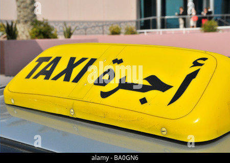 Abu Dhabi close up of roof mounted yellow bilingual taxi cab sign - Stock Photo