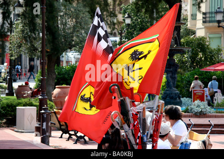 Street scene in Monte Carlo dominated by an umbrella stand and two Ferrari flags - Stock Photo