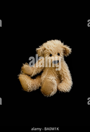 Cute hand made honey coloured teddy bear with a black stiched nose and sparse fur on a black background. - Stock Photo