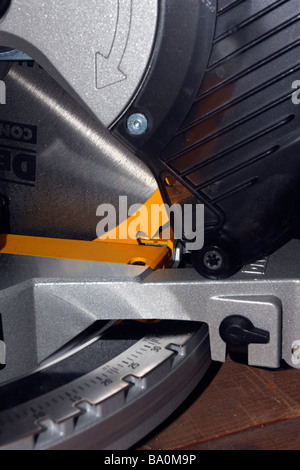 Closeup of cutting area of DeWalt chopbox miter saw blade showing arrow and yellow. - Stock Photo
