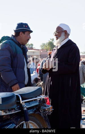 Two local Moroccan men in conversation together on the place Jemaa El Fna in Marrakech - Stock Photo