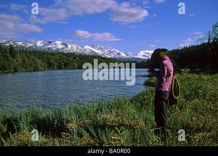 a woman fly fisherman ties on a fly for grayling in a alpine lake in alaska - Stock Photo
