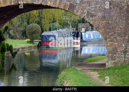 Longboat on Grand Union Canal Approaching Bridge - Stock Photo