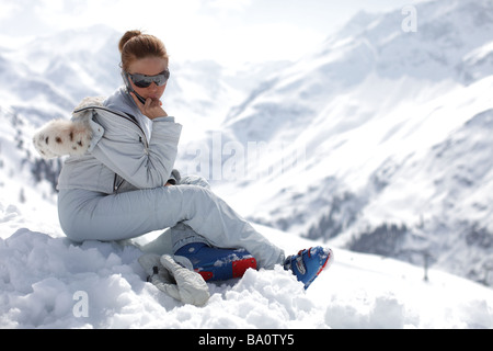 Female skiing model wearing white ski gear using a mobile phone whilst sitting in the snow up a mountain with a - Stock Photo