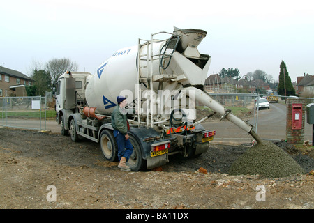 Pouring concrete from a cement mixer on a building site in England - Stock Photo