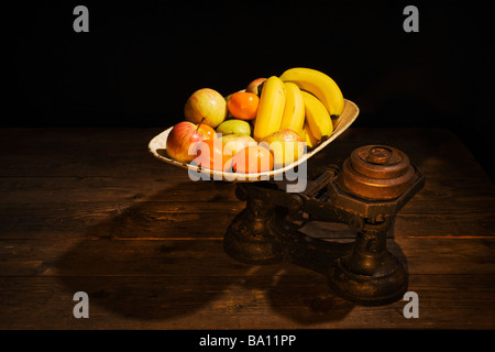 Mixed fruit on antique scales. - Stock Photo