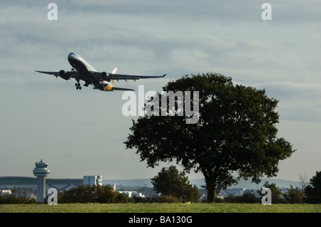 The wheels are retracting into the aircraft fuselage as a Monarch Airlines Jet airplane takes off from Gatwick - Stock Photo