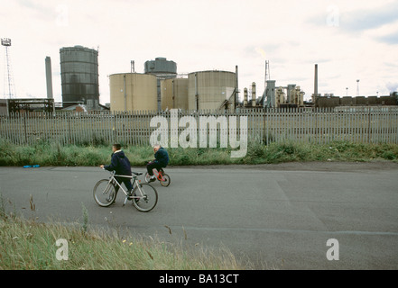 Two boys cycling past Redcar Steelworks Teesside - Stock Photo