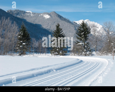 Machine made ski-track at the footage of woody mountains, plenty of snow, Austria, Achenkirch, near Innsbruck. - Stock Photo