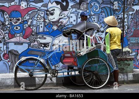 Cycle Rickshaw against Grafitti wall, Yogyakarta, Indonesia.