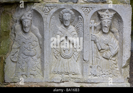 Relief carving of 3 figures. A carved relief on the side  of a coffin in the famous old Abbey. - Stock Photo