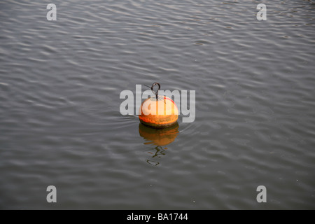 n orange buoy floating mid stream on the River Thames near Richmond Lock and Twickenham Bridge. - Stock Photo