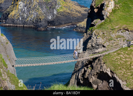 The return trip. A tourist crosses the famous rope bridge over the bright blue and green water from the island  - Stock Photo