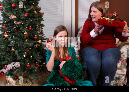 Mom and daughter exchanging Christmas gifts - Stock Photo