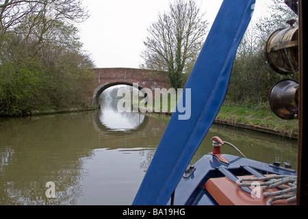 Longboat Approaching Bridge on Grand Union Canal - Stock Photo