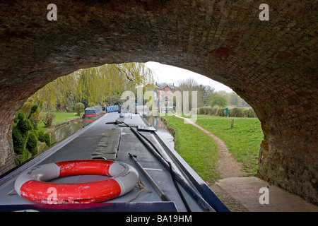 Longboat Going Under Bridge on Grand Union Canal - Stock Photo