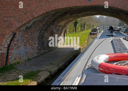 Longboat Boat Going Under Bridge on Grand Union Canal - Stock Photo