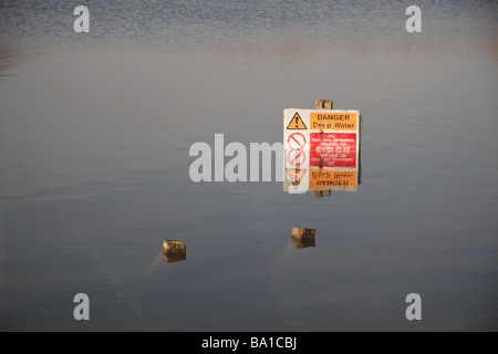 A partially submerged 'Danger Deep Water' sign in a lake of Bedfont Lakes Country Park, Bedfont, Middlex, UK. - Stock Photo