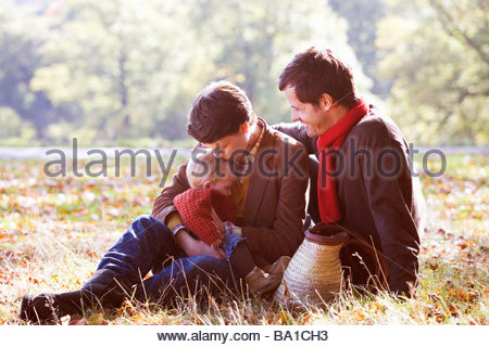 A young family sitting on the grass in autumn time - Stock Photo