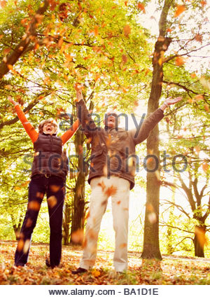 A senior couple throwing autumn leaves in the air - Stock Photo