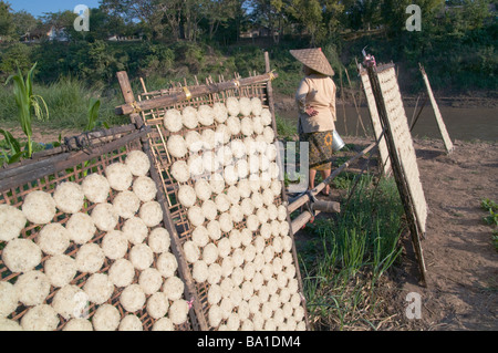 LAOS.RICE CAKES DRYING IN THE SUN IN A VILLAGE BY THE MEKONG RIVER Photo Julio Etchart - Stock Photo