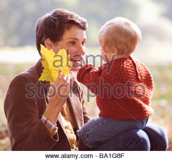 A young mother showing an autumn leaf to her baby - Stock Photo